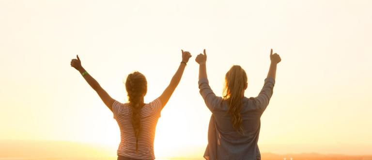 Two women with thumbs up in facing a sunset